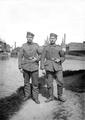 Zwei Soldaten vor Fluss und Industriegelände