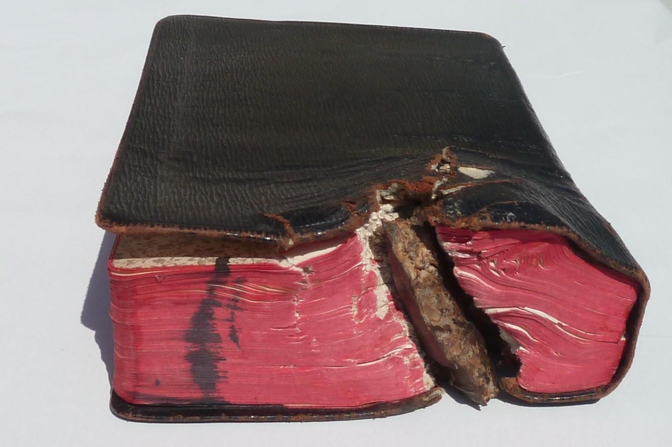Dieses Bild einer mit Bibel mit Granatsplitter wurde von Gottfried Geiler unter einer CC BY-SA 3.0 Lizenz auf der public-domain-webseite www.europeana.org publiziert.