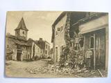 Ansichtskarte eines zerstörten Ortes mit posierenden Soldaten.
